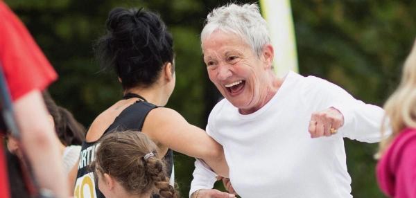 Middle-aged woman having fun dancing with young people