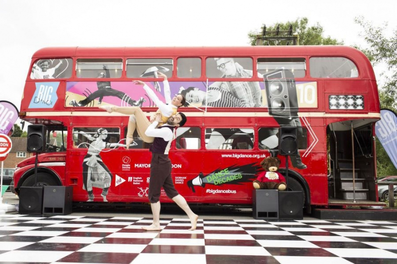 London route-master bus with outdoor dance-floor and dancer in front