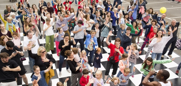 Black and white checked dancefloor, with people of all ages dancing together and smiling
