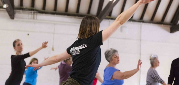Woman in New Adventures t-shirt leads dance in studio space