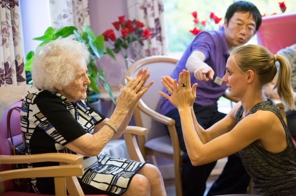 Elderly woman and helper doing clapping activity